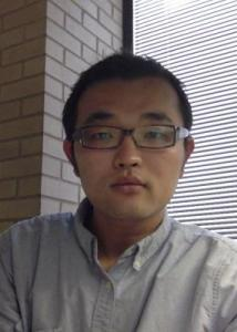 Headshot of Junjun Yin with short black hair, thick glasses and a light blue shirt.